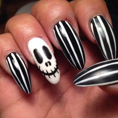 Pinstripes with a skull accent. | 27 Delightfully Spooky Ideas For Halloween Nail Art