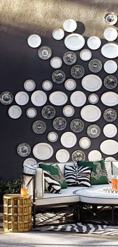 A solid black wall is brought to life with an eye catching display of all white plates and black and white Spode transferware plates, and then grounded by a great zebra-print area rug.