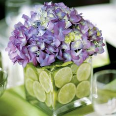 Rachel and Eddie opted for small, square, glass vases stuffed with sliced limes and purple hydrangeas to sit at the center of the tables.