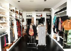 Heidi Gores - Huge walk-in closet with floor to ceiling built-in shelves, shoe shelves, garment cart and glossy espresso wood floors.