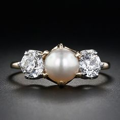 This classic Victorian-era three-stone ring, crafted in rose-yellow gold and platinum, highlights a shimmering, velvety light cream color natural pearl. The pearl is flanked left and right by beautiful old European-cut diamonds weighing .75 carat total.
