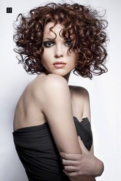 Women's medium length spiral perm curly hairstyles, with chocolate brown hair and full parted bangs.