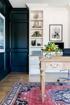 dark grey paneled walls, white built-in shelves and drawers, antique table