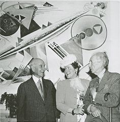 "Guggenheim, Hilla Rebay and Frank Lloyd Wright in front of Bauer's painting ""White Fugue"", 1930s."