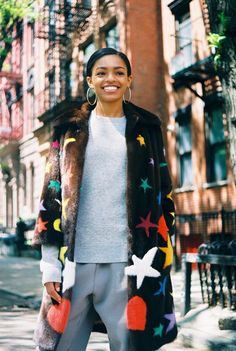 Selah Marley in a Gucci mink fur coat with star, lightning, heart, and moon intarsia, gray sweater, and gray sweatpants