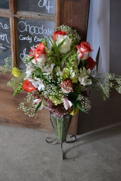 White Coral Fire Rose Bouquet with White Alstroemeria, Yellow Snap Dragon, Grass, Baby's Breath, and added fillers in a Glass and Metal Vase.