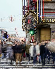 People crossing by Madame Tussaud at Dam Square in Amsterdam. | by Robert Diel