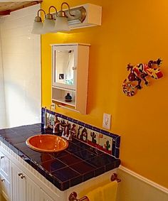 Colorful bathroom countertop tile and inset ceramic sink.