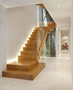 Arcways custom stepped stairway with unique hidden wall side illumination. The white oak contrasts beautifully with the glass rail & white floors & walls. Arcways is your single source custom stairway expert. http://www.arcways.com