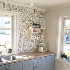 Kitchen corner in blue.  Retro in design with blue floral wallpaper but would still suit a country cottage.