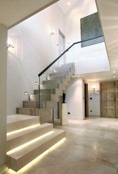 escalier droit en béton avec rambarde en verre, éclairage indirect et spots LED encastrés au mur