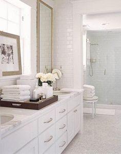 Clean crisp white bathroom design with white carrara marble hexagon floors tiles and white carrara marble counter tops, white bathroom cabinets, chrome mirror, subway tiles and white stool!