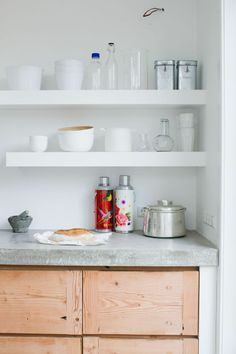 Concrete counter top / White wall with two shelves for storage
