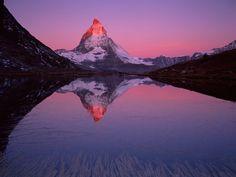Matterhorn; photograph by Verena Popp-Hackner. Radiant at sunrise, the Matterhorn towers over Riffel Lake near Zermatt, Switzerland.