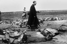 Military chaplain walks among the corpses of French soldiers on the Western Front.