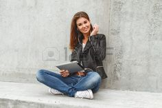 Girl with a tablet and headphones in hands sits on a concrete wall. Online education students