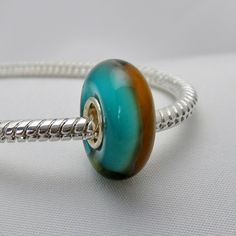 Amber Tealicious - Beautiful murano with teal and amber vertical stripes. Sterling silver, single core. Unthreaded. Approximate dimensions: 15 mm x 9 mm. Hole measures 4 mm. This is an Ovarian Cancer fundraising charm. One dollar donated to the cause for every charm sold. #charity #ovariancancer #eurobeads