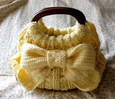 A cute crochet handbag with a sweet bow on the front and bamboo handles for easy carrying. Crochet Materials: Japanese size 5/0 & 8/0 crochet hooks (3.0 & 5.0 mm.) 300g (825m) Smoothness Si…