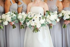 classic all white bridesmaids bouquets of white garden roses, white ranunculus, button chamomile, white spray roses, dusty miller and eucalyptus. the bride chose to add highlights of white anemone in her bridal bouquet.
