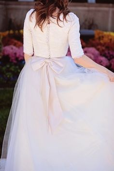 Long Sleeve Wedding Dress, Tulle Ball Gown - Michelle Style - Avail & Company, LLC  Modest Vintage Puffy Tulle Wedding Dress with delicate buttons and a pastel pink bow. A puffy skirt made of tulle that gracefully flows down and out into chapel length train and a lace bodice with elbow length sleeves. Perfect for an Outdoor Wedding.