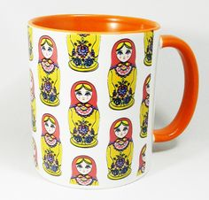 Traditional Russian Doll Design Ceramic Mug with an orange glazed handle and inner. A high quality ceramic mug withan orange glazed handle and inner. Dishwasher proof. Height is 9.5cm, diameter 8.2cm, with a capacity of 310 ml . From the Series 1 The Original Line by Half A Donkey www.halfadonkey.co.uk
