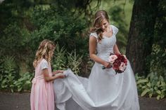 Matt Shumate Photography photo of little flower girl in light pink dress helping the sweet bride with her wedding dress