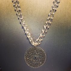 Nicci Necklace - This beautiful necklace is made of 3 strands of silver pyrite chain accented with a large antique silver ornate medallion with blue zircon rhinestones - $72.00