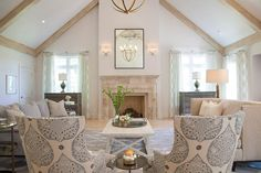 Transitional living room features a vaulted ceiling lined with light wood beams over a limestone fireplace under an antiqued mirror illuminated by 2 Light Cross Bouillotte Sconces flanked by gray chests placed in front of windows dressed in gray lattice curtains.