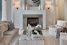 Love the cleanliness of this living room. The fireplace and the sconces framed off to each side. Simple stone/marble facade. What is it? Color of the walls with the white molding/trim work. Awesome! Snow & Sparkle