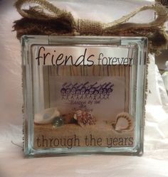 "Glass block ""Friends Forever Through The Years"". Sand in the bottom, seashells, rocks from the beach and a few flat marbles that look like sea glass. A burlap bow on the top. A clear acrylic photo frame inside to hold a special beach photo. (Hint: when making one of these- put the opening on the side so the photo frame can be slipped in easily - otherwise you can't turn it once inside. ) Like my stick people picture?"