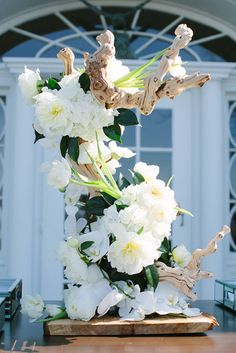 floral arrangement for entrance of reception with driftwood by Holly Chapple Flowers http://www.hollychappleflowers.com/