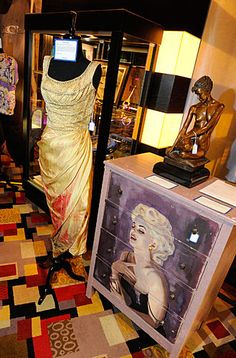 Marilyn Monroe's Ceil Chapman evening gown is displayed next to Anna Nicole Smith's custom painted Marilyn Monroe dresser.