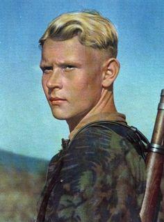 """La coupe du soldat AllemandLa mode de cette fin des années 40 chez les soldats allemands est d'avoir une longue mèche dissimulée sous son casque , son calot ou sa casquette.  En effet, si d'extérieur le soldat allemand est bien rasé sur les côtés, parfois même à blanc, il n'en est pas de même pour le haut.  La mode Zazou est suivie de très près ! La musique et les artistes entraîne chez les nouvelles recrues de l'armée allemande, cette coupe très particulière à la """"houppette""""."""