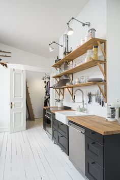 Open kitchen in wood and black in a charming one room Swedish apartment
