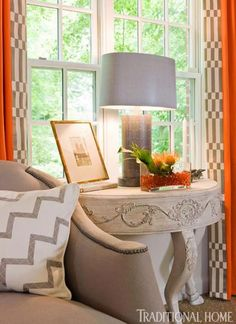 Showhouse Rooms in Orange | Traditional Home - the sofa's gray upholstery is balanced by checks that edge soaring drapery panels.