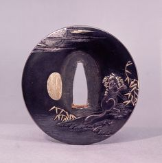 Tsuba decorated with a magic fox disguising itself as a woman shibuichi -Iwamoto Konkan
