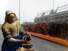 Melkmeisje van Vermeer zorgt voor de wachtende bij het Rijksmuseum tijdens de opening 13 april 2013.