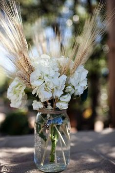 Garden flowers and wheat in a mason jar with twine creates a modern country display...