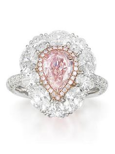A coloured diamond and diamond ring. The pear-shaped modified brilliant-cut fancy light brownish pink diamond, weighing 1.21 carats, within a brilliant-cut pink hue diamond surround, to an oval-cut and heart-shaped colourless diamond surround and single-cut diamond half-hoop, mounted in 18k white gold, the remaining diamonds estimated to weigh approximately 2.90 carats in total.