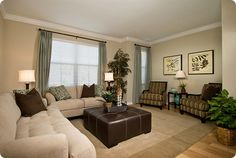 tan and green living room with large cream sectional, square ottoman and striped chairs on seagrass rug