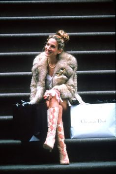 Stoop kid: Carrie sits with a fur coat, snakeskin boots, and Dior shopping bag to top it off