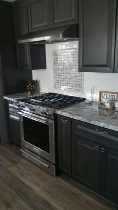 Viscount white granite, dark Charcoal cabinets, white subway tile backsplash with basket weave inset above stove.