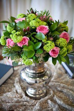 Pink garden roses, kermit green viburnum centerpiece in silver vase.