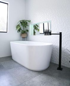 White round edged freestanding stone bathtub and matte black freestanding bath f. White round edged freestanding stone bathtub and matte black freestanding bath filler mixer. Bathroom Concrete Floor, Polished Concrete Tiles, Small Bathroom Tiles, Modern Bathroom Design, Bathroom Interior, Textured Tiles Bathroom, Bathroom Feature Wall Tile, Bathroom Prints, White Bathrooms