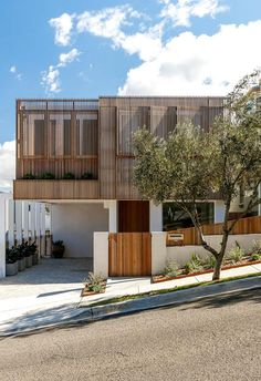 Timber screens create a striking facade for this home and complements the slatted timber fencing that lines the exterior.