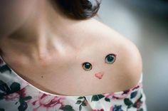 Minimalist cat tattoo on the left shoulder.