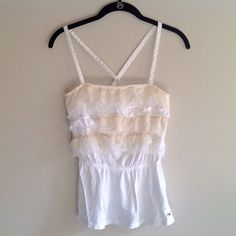 Hollister white ruffled tank Hollister white ruffled tank-top. Straps criss-cross in the back and cinches at the waist. Size medium. Bundle 2 or more items to save! Have this tank top in purple, green and grey too. Hollister Tops Tank Tops