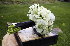 Lucia will carry a petite bouquet of white scabiosa flowers wrapped in raffia with the stems showing.
