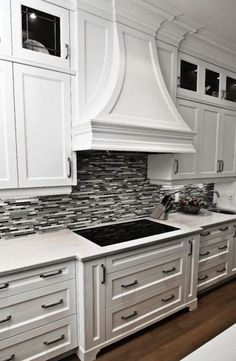 Black or Grey Linear Glass Tile Backsplash with Crisp White Cabinetry and Marble Countertops