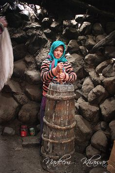 Girl making butter in Baba Ghundi in the Chuparsan Valley of Gojal, Afghanistan. Baba Ghundi is the shrine of the famous Pir of Ghund from Afghanistan who is celebrated in legend as the saint who brought devastation to the valley. The people of Hunza Valley revere the saint and believe children who are a problem have only to taste the mud from a stream near Baba Ghundi to become obedient and well behaved.